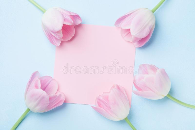 Wedding mockup with pink paper list and tulip flowers on blue table top view. Beautiful floral pattern. Flat lay style. stock photo