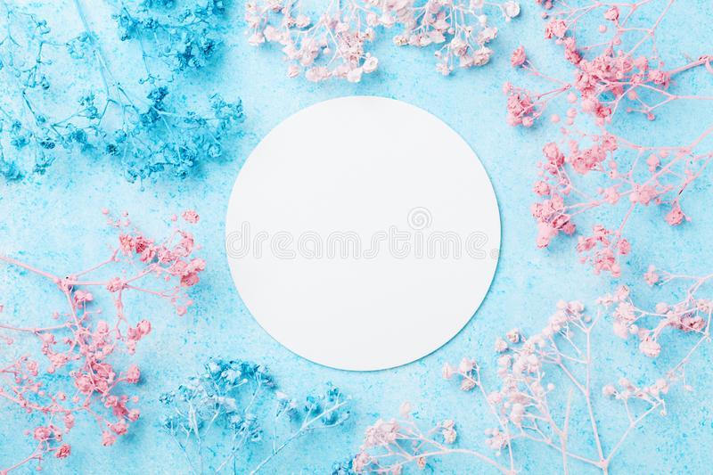 Wedding mockup with white paper list and flowers on blue pastel table top view. Beautiful floral pattern. Flat lay . Spring card. Wedding mockup with white stock photo