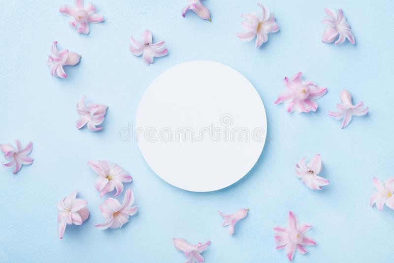 Wedding mockup with white paper list and pink flowers on blue background top view. Beautiful floral pattern. Flat lay style. Wedding mockup with white paper stock image