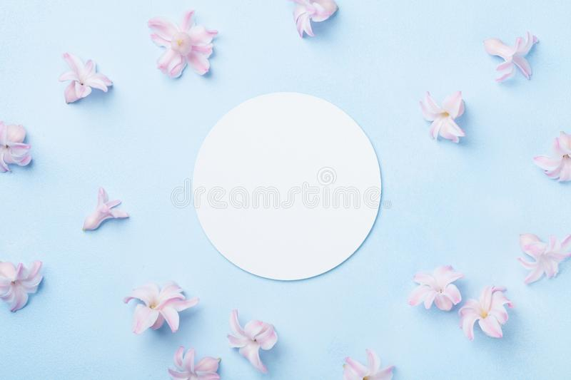 Wedding mockup with white paper list and pink flowers on blue table from above. Beautiful floral pattern. Flat lay style. Wedding mockup with white paper list stock photo