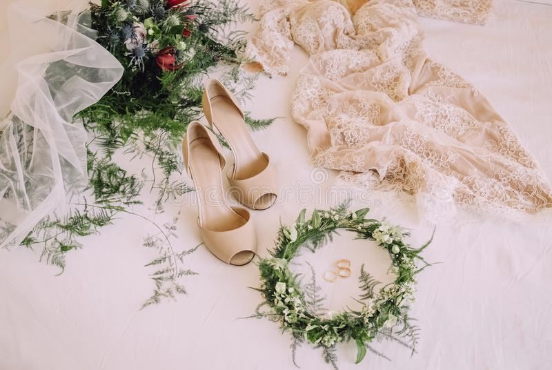 Headdress wreath decorated wedding ring and dress. Wedding morning composition of the great wedding bouquet, wedding dress, wreath, veil and shoes on bed stock photography
