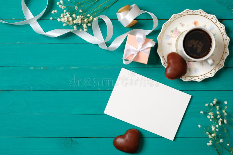 Wedding morning concept. Invitation card, heart-shaped chocolate, gift box, cup of coffee, daisy flowers. Stylish minimal women`s. Desk. Flat lay composition royalty free stock photography