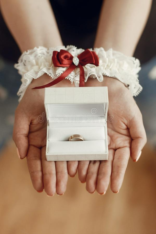 Wedding morning preparation concept. woman hands in silk garter. Holding golden ring in box. space for text stock photos