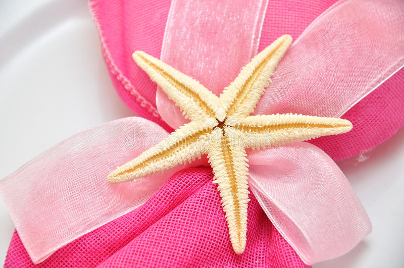 Wedding napkin. An pink formal napkin with star at a place setting for wedding or special event stock photography