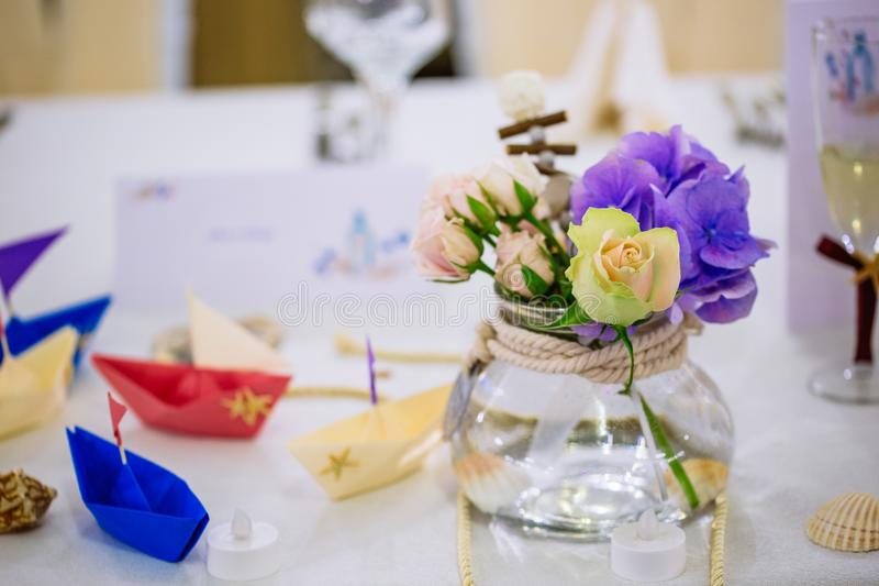 Wedding nautical table arrangement with flower bouquet and origami boats. Wedding nautical table arrangement with bouquet and origami boats, restaurant party royalty free stock photos