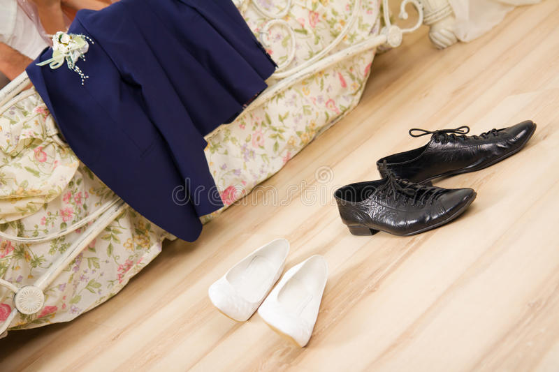 Wedding night. Disrobed wedding clothes, suit and shoes near a bed stock photos