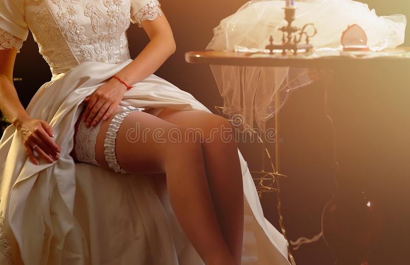 Wedding night preparing garter. Bride undressing. Wedding night preparing garter. Bride undressing and put veil on table. Candle illuminates house. Girl stock photo