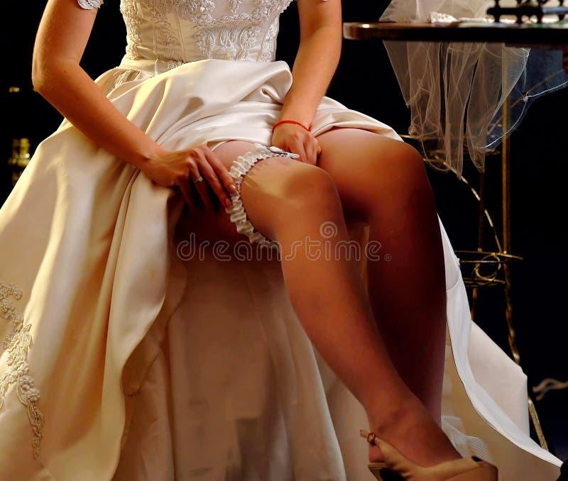 Wedding night preparing garter. Bride undressing. Wedding night preparing garter. Bride undressing and put veil on table. Candle illuminates house. Jewelry box royalty free stock photography
