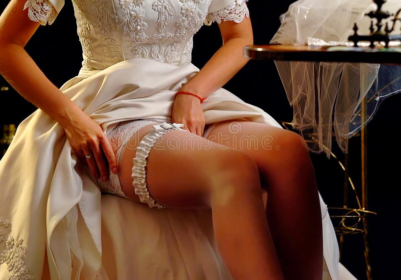 Wedding night preparing garter. Bride undressing. Wedding night preparing garter. Bride undressing and put veil on table. Well-groomed legs before the wedding stock photo