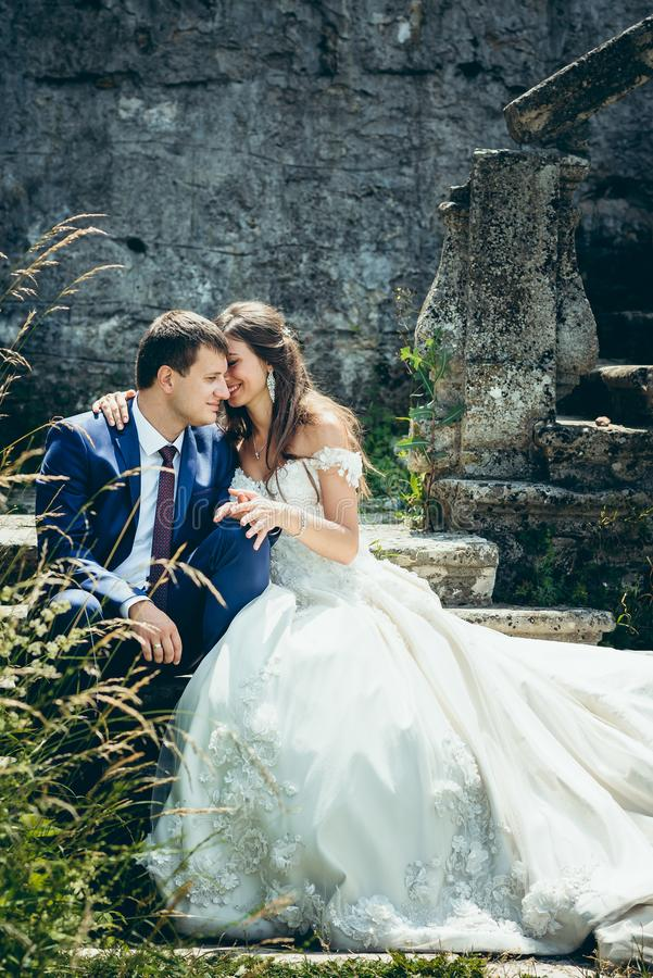 Wedding outdoor shot of the beautiful smiling newlywed couple holding hands and sitting on the old castle stairs. Wedding outdoor shot of the beautiful smiling royalty free stock image