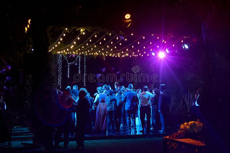 Wedding party dancing at night, outdoor weddings. Purple light background with lights and guests having fun, dance floor people dancing stock image