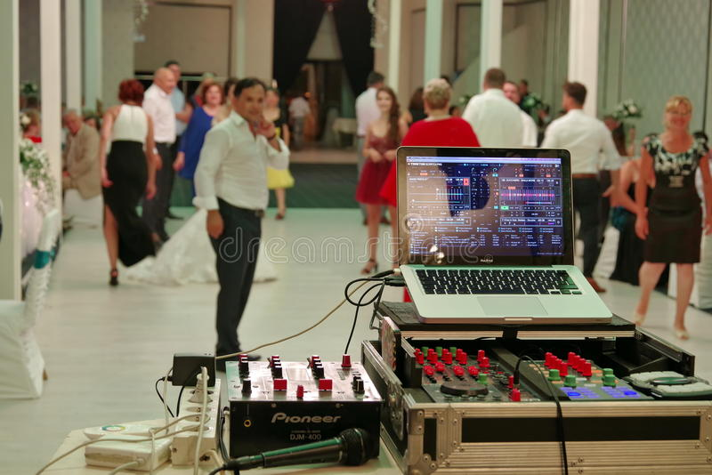 Wedding party. People dancing. Dj equipment. Dj equipment at a wedding party, with people dancing in the background stock image
