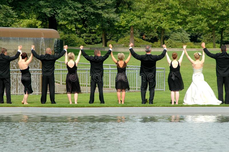 Wedding party hands up outdoors. SEATTLE, WA. AUGUST 11, 2007. CIRCA: Wedding party taking pictures with their hands up in unity in a public park outdoors