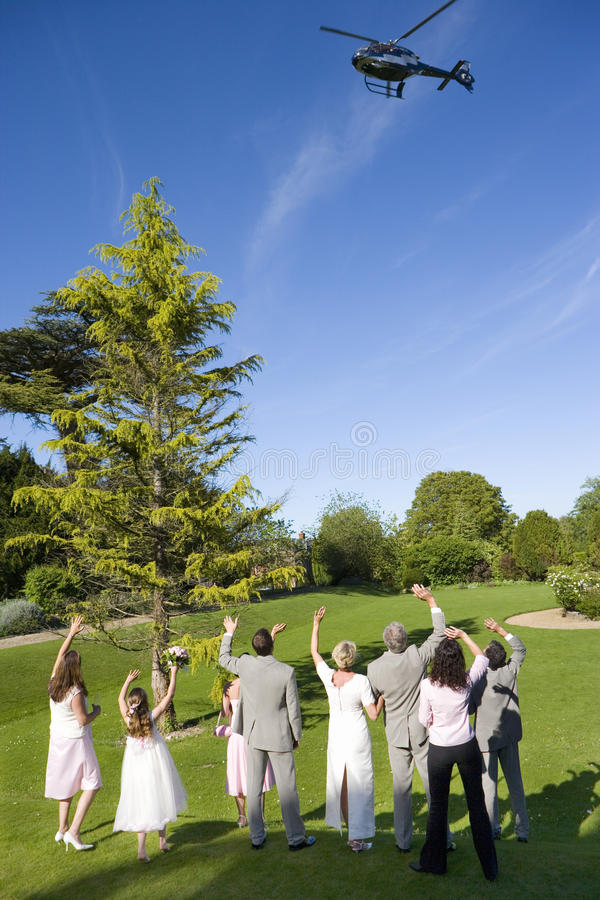 Wedding party waving at helicopter departing, rear view stock photography