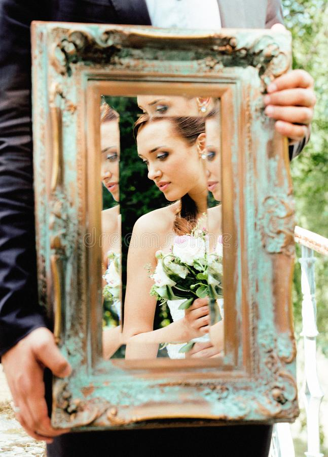 Wedding people concept, groom holding vintage mirror with bride reflection royalty free stock photos