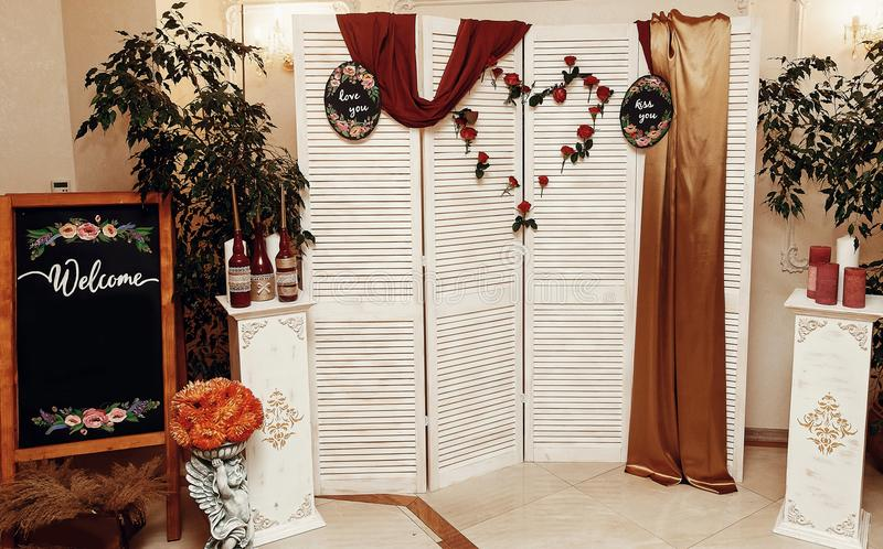 Wedding photo booth zone and welcome board. rustic wooden wall w. Ith flowers, red roses heart and love signs, decorated backdrop and empty chalkboard. wedding stock photo