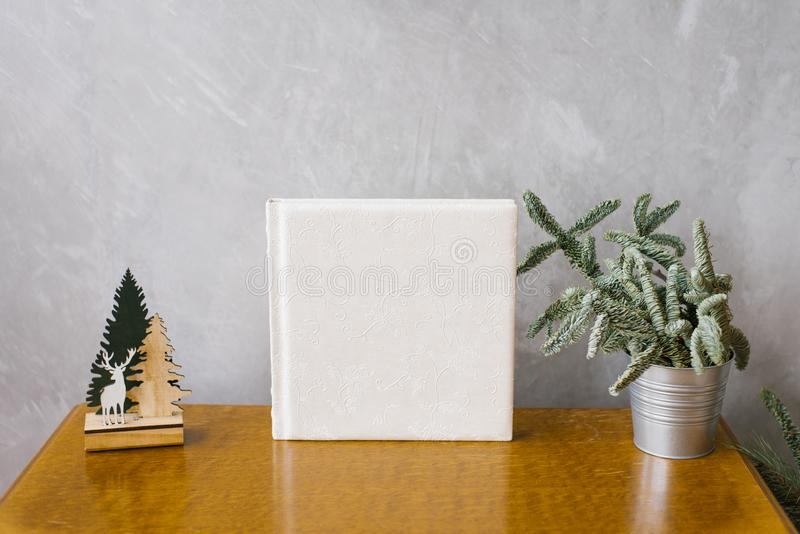 Wedding photobook in white leather cover surrounded by a Christmas tree. In a metal bucket royalty free stock image