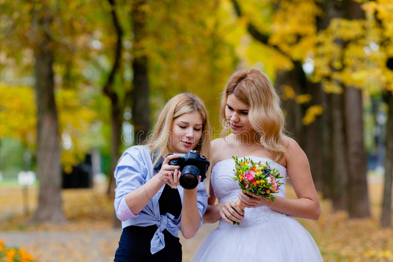 Wedding photographer discussing with the bride recently taken photos. In the autumn park stock photo