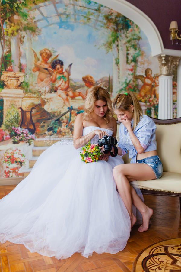 Wedding photographer discussing with the bride recently taken photos. In the studio royalty free stock photography
