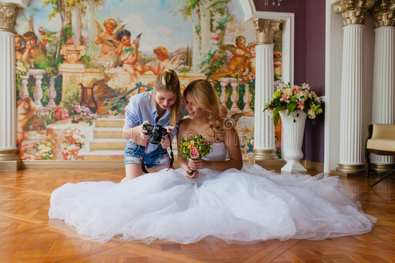 Wedding photographer discussing with the bride recently taken photos. In the studio stock photos