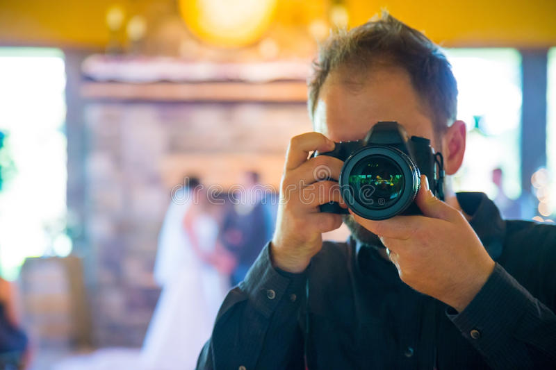 Wedding Photographer Self Portrait. Wedding photographer with a DSLR and professional lens shooting photos of the bride and groom during the ceremony, self stock image