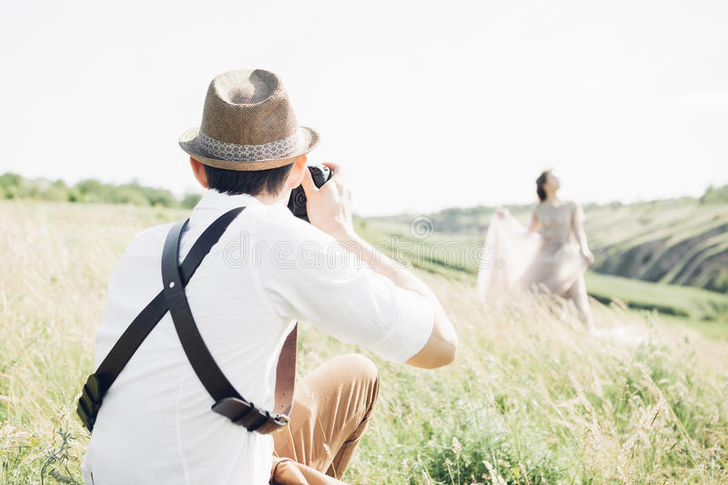 Wedding photographer takes pictures of bride and groom in nature, fine art photo. Wedding photographer takes pictures of bride and groom in nature in summer royalty free stock photos