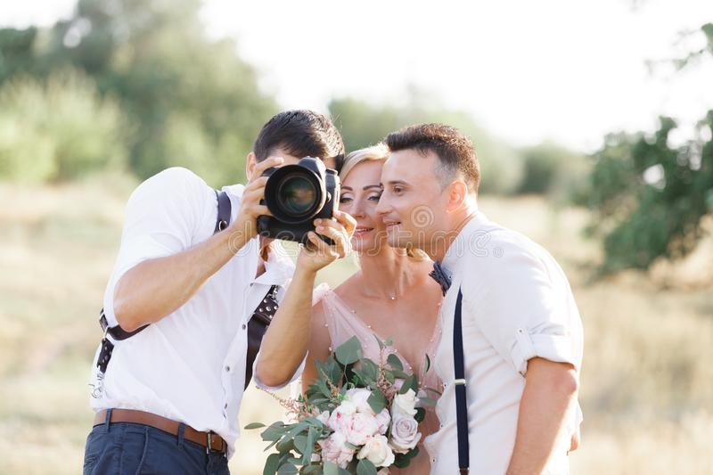 Wedding photographer takes pictures of bride and groom. In nature. photographer shows just taken photos to wedding couple stock photography