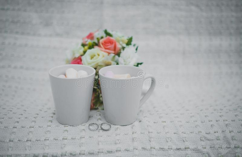 Wedding photography. wedding details winter wedding. two white cups with and marshmallows, a bridal bouquet and rings royalty free stock photos