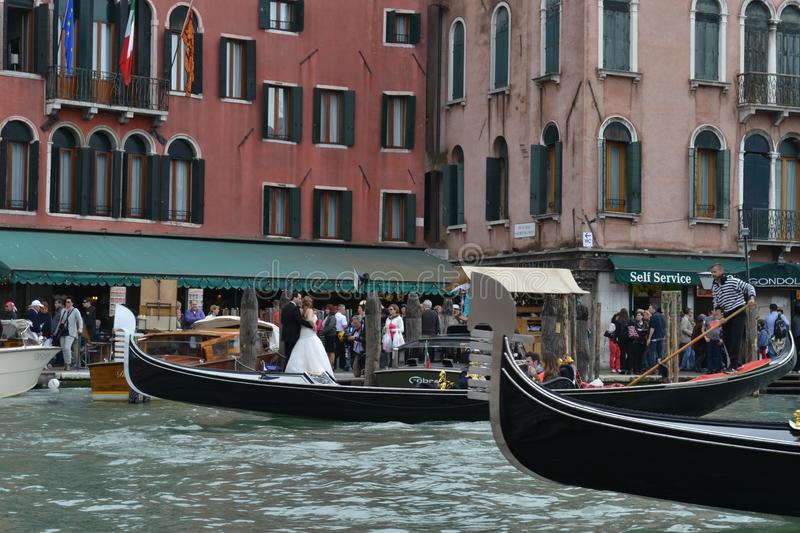 Wedding photography at the Grand Canal and the Rialto bridge with gondolas passing by. royalty free stock image