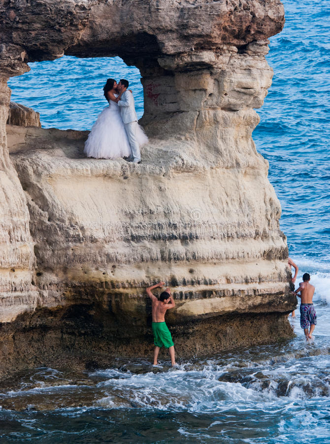 Wedding photography of new married couples. Ayia Napa, Cyprus - 12 July 2013: Wedding photography of new married couples with teenage boys in the sea at famous stock image