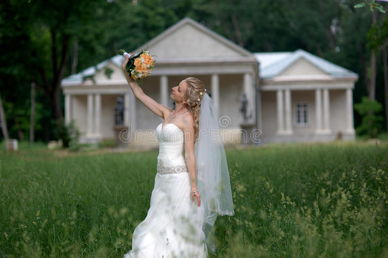 Wedding Portrait Of Beautiful Happy Bride wearing white wedding. Dress holding a bouquet of rose flowers posing in green park stock photo