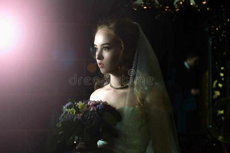 Wedding portrait. Portrait of a girl in a wedding dress with a veil on a dark background. royalty free stock photo