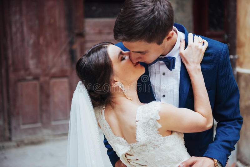 Wedding portrait of a happy couple. Stand and kissing stock images