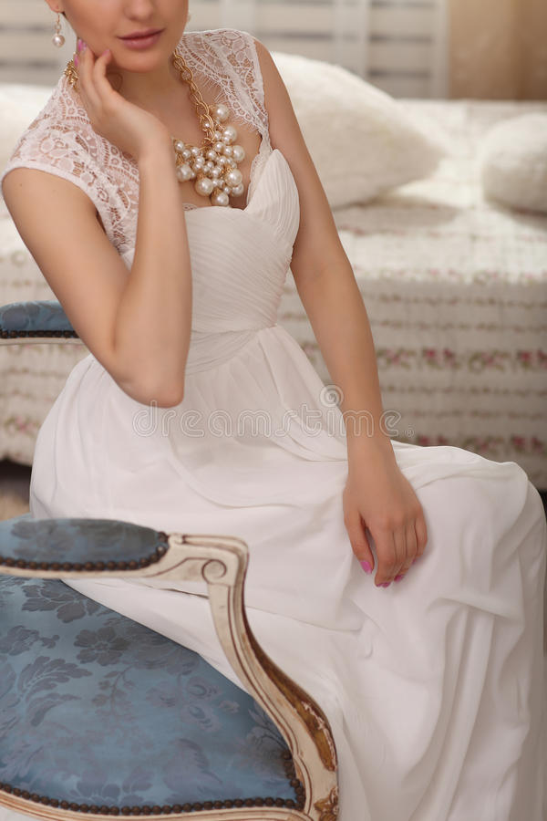 Wedding preparation. Beautiful young bride in white wedding dress indoors closeup. Luxury model sitting on vintage chair at home i royalty free stock photography