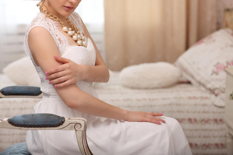 Wedding preparation. Beautiful young bride in white wedding dress indoors. Luxuty model sitting on vintage blue chair at home in s stock image