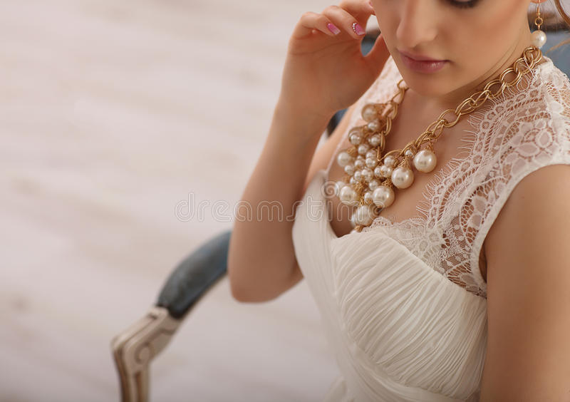 Wedding preparation. Beautiful young bride in white wedding dress and perls indoors. Luxury model sitting on vintage chair at home stock photography