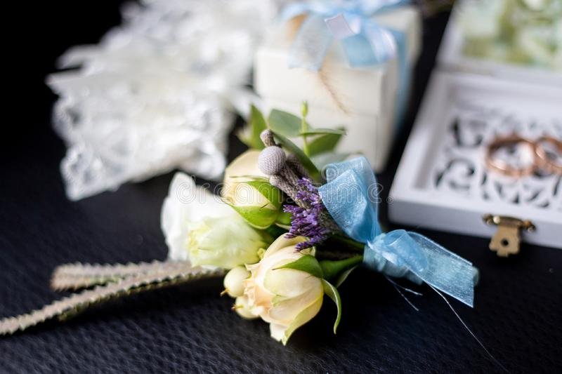 Foreground boutonniere, wedding rings and the garter of the bride in the background royalty free stock image