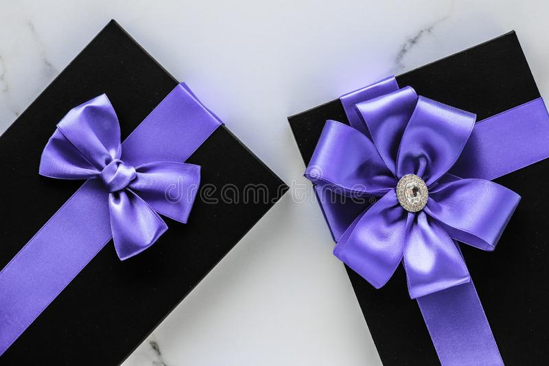 Luxury holiday gifts with lavender silk ribbon and bow on marble background stock photo
