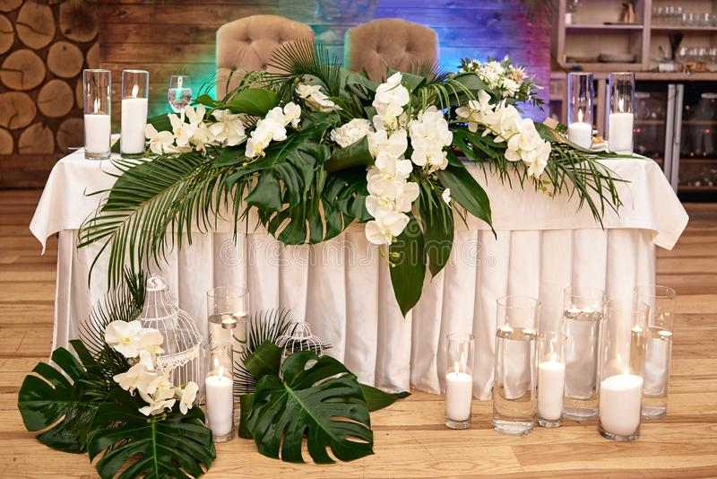 Wedding presidium in restaurant, copy space. Banquet table for newlyweds with monstera palm leaves, orchid flowers and candles. stock photography