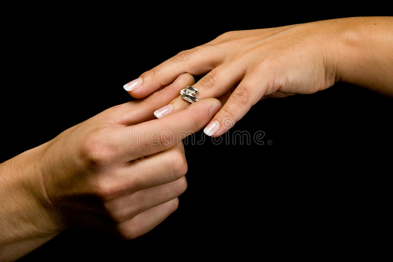 Wedding proposal. Putting a wedding ring on the finger royalty free stock image