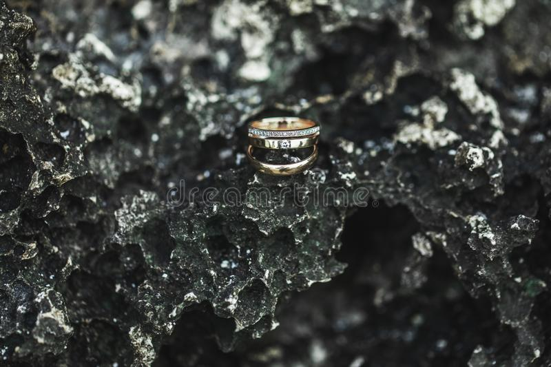 Wedding and proposal rings on black stone texture. Three wedding and proposal rings with gemstones on stone black textured volcanic background close up royalty free stock photo