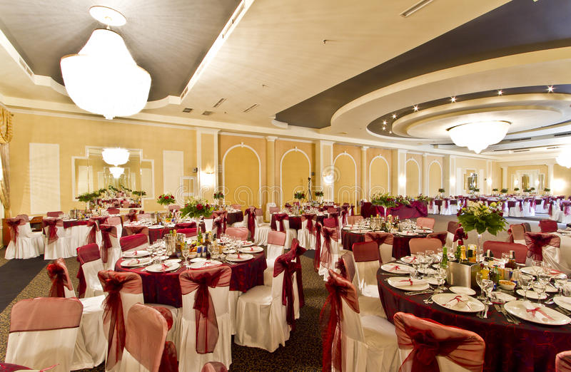 Wedding reception hall. With table and chair covers and bright chandeliers stock photo