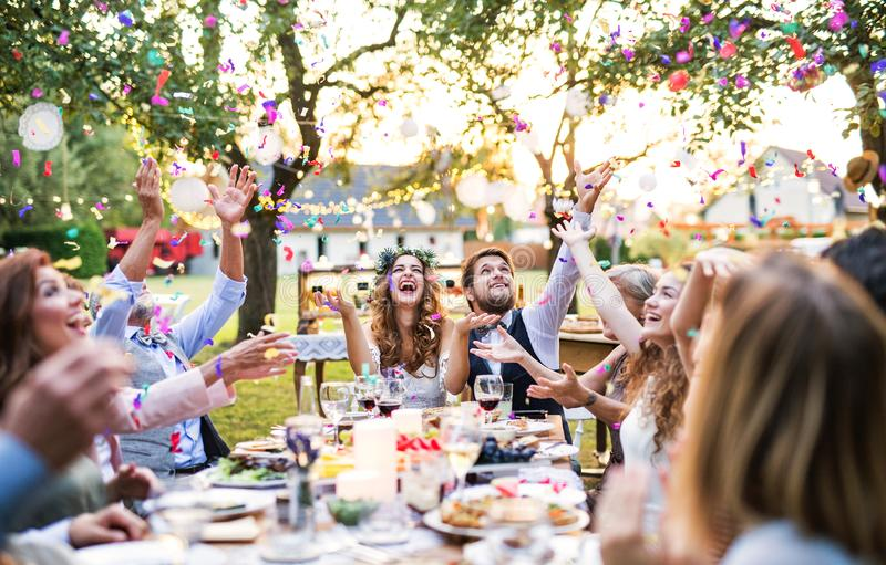 Bride and groom with guests at wedding reception outside in the backyard. Wedding reception outside in the backyard. Bride and groom with family and guests stock image