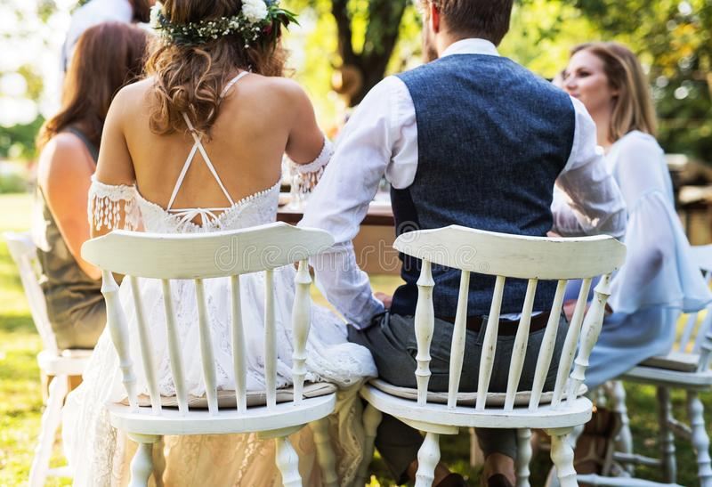 Bride and groom with guests at wedding reception outside in the backyard. stock image