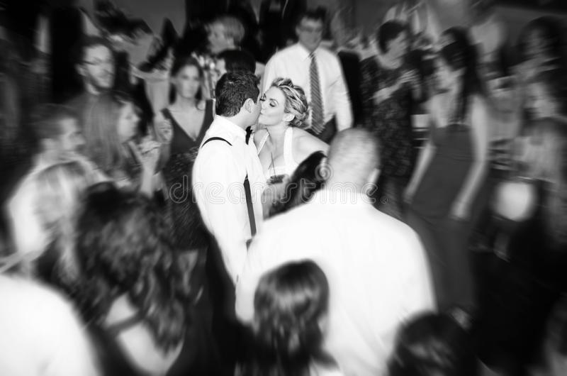 Wedding reception party. Movement of a dancing party creates a blur around a kissing bride and groom