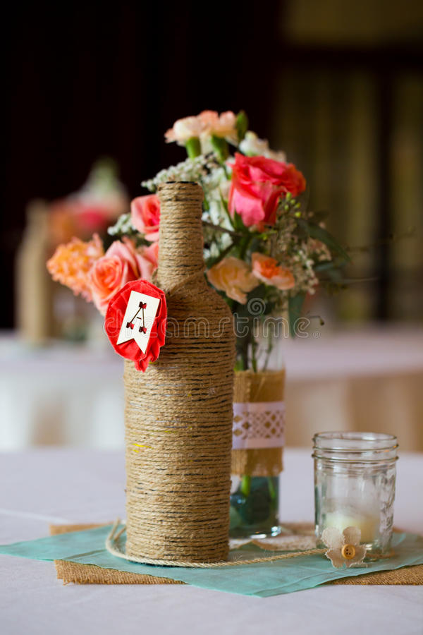 Wedding Reception Table Centerpieces. DIY wedding decor table centerpieces with wine bottles wrapped in burlap twine and rose flowers stock photography