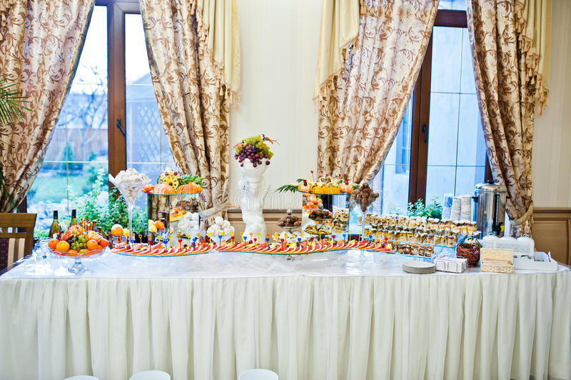 Wedding reception table of fruits and cakes. stock photo