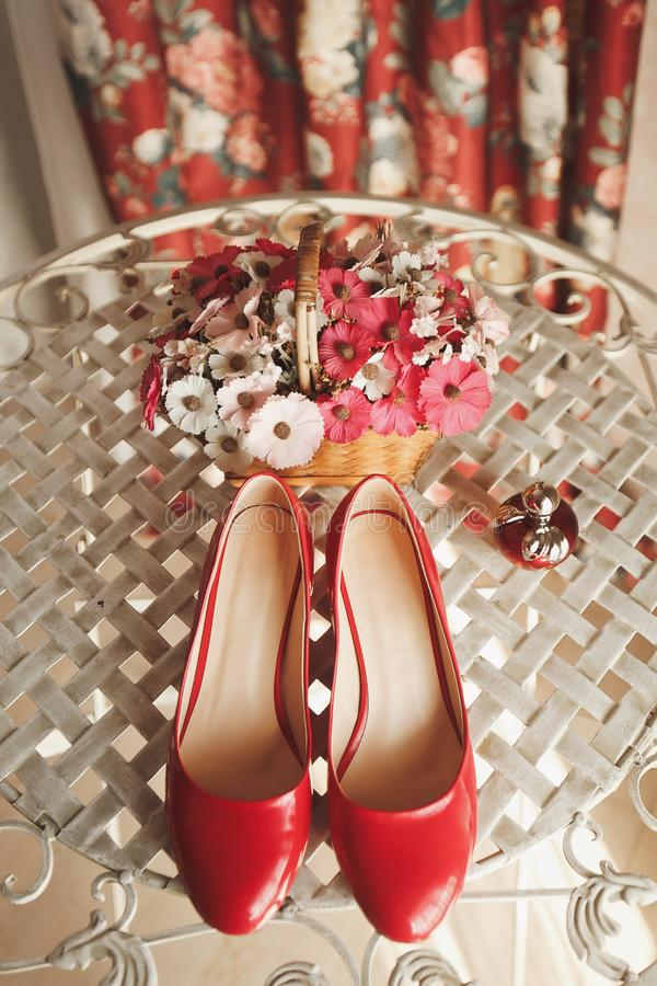 Wedding red designer bride shoes, perfume bottle and decorative flowers in a basket on the coffee table. Women`s new luxury moder stock image