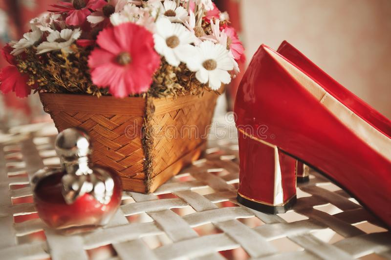 Wedding red designer bride shoes, perfume bottle and decorative flowers in a basket on the coffee table. Women`s new luxury moder royalty free stock image