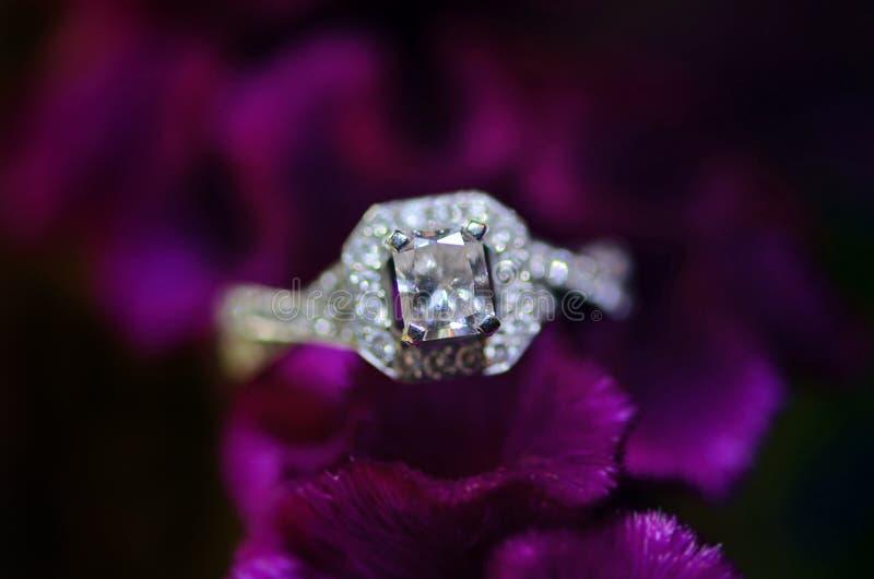 Wedding ring. Her diamond wedding ring in bouquet of purple flowers stock photo